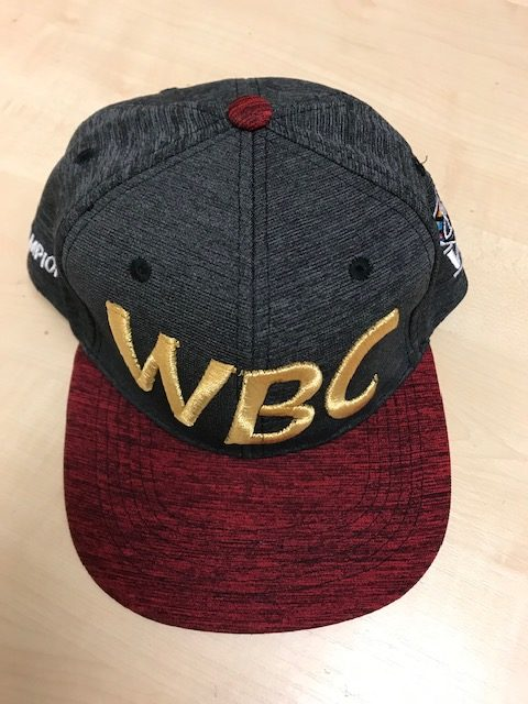 Front view of a red and grey WBC Baseball Cap with WBC logo embroidered in gold on the front