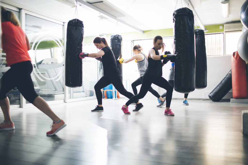 Group of women practicing punching boxing bag in the gym