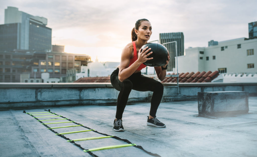 Female athlete doing squats holding a medicine ball standing on a rooftop. Woman doing workout using medicine ball with an agility ladder by her side on rooftop.