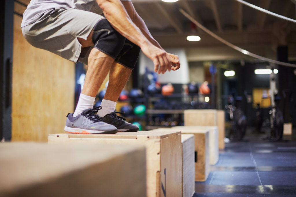 Male on top of box jump exercise in squat position.