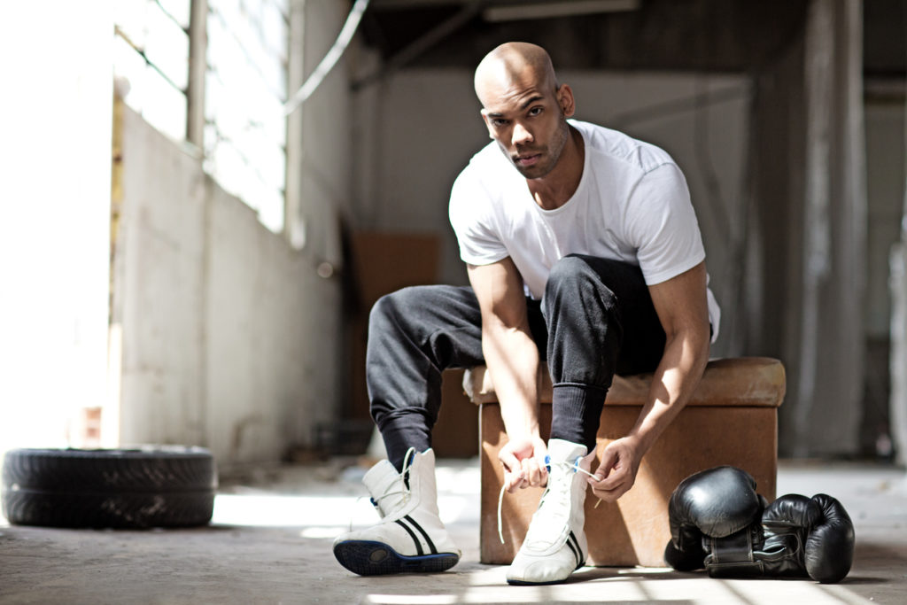 Young male boxer in abandoned warehouse tying his white boxing shoes