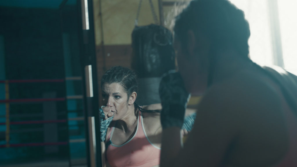 Woman practicing shadow boxing in front of a mirror