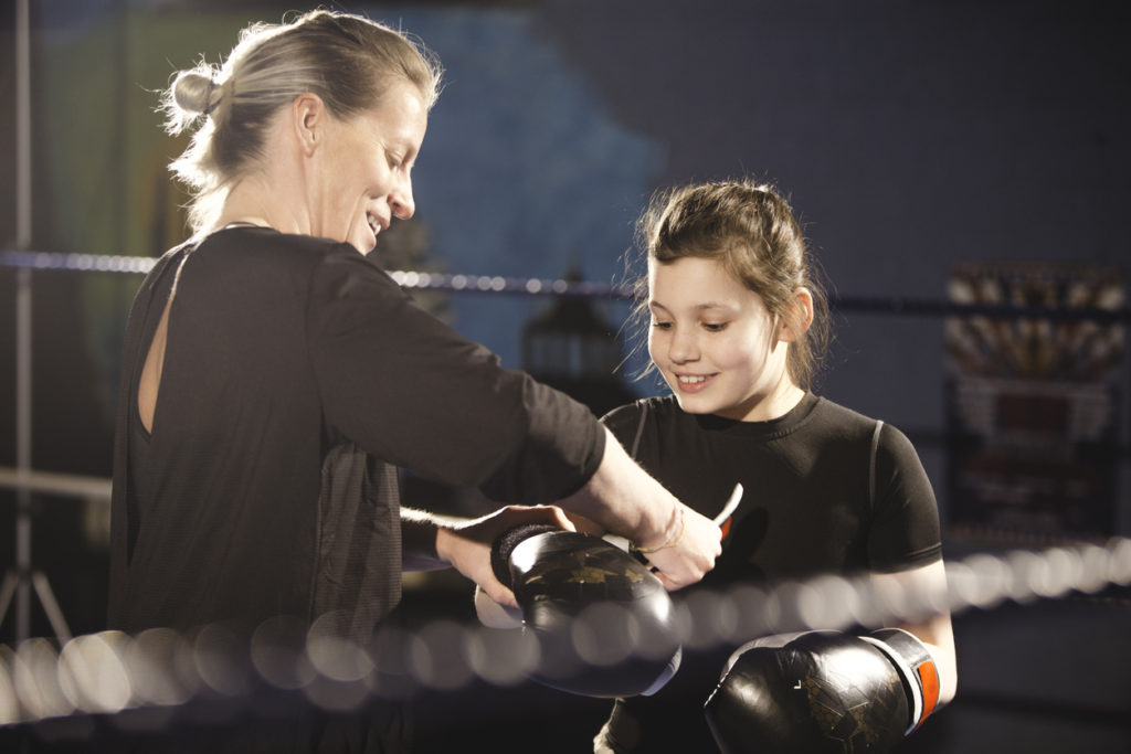 Female boxing instructor helping a young female student to put on her gloves.