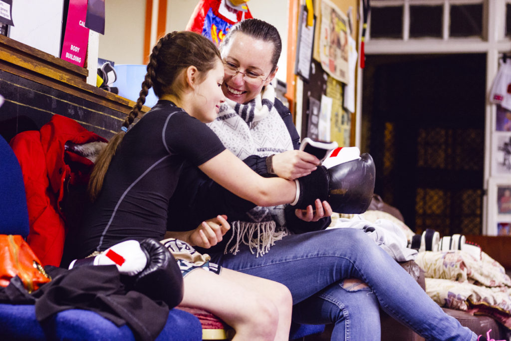 Young female boxer is sitting in the gym next to her mother while she helps her put on her boxing gloves. The mother is smiling happily, clearly proud of her young daughter.