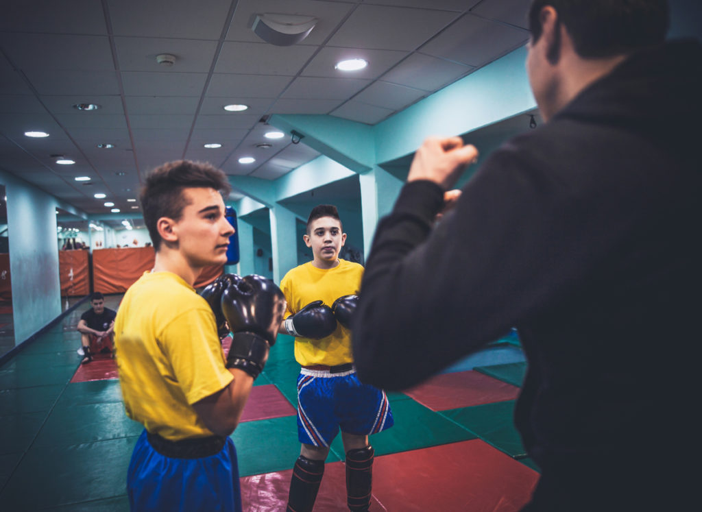 Two boys wearing boxing gloves taking instruction from boxing coach.