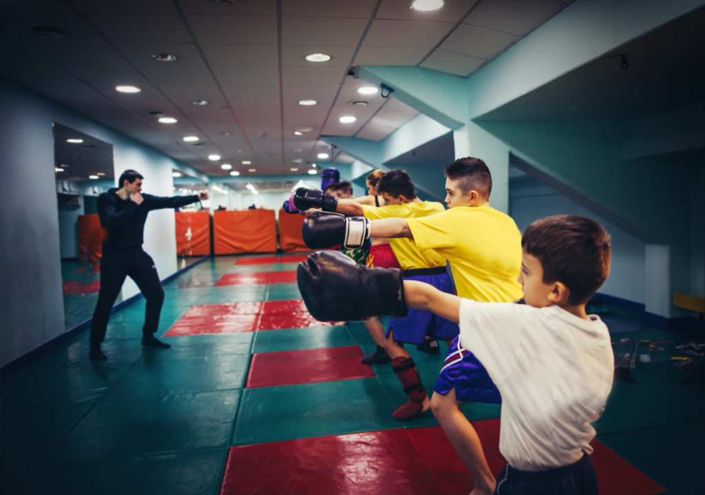 Young boys in a line at a boxing gym shadow boxing and copying instructor.