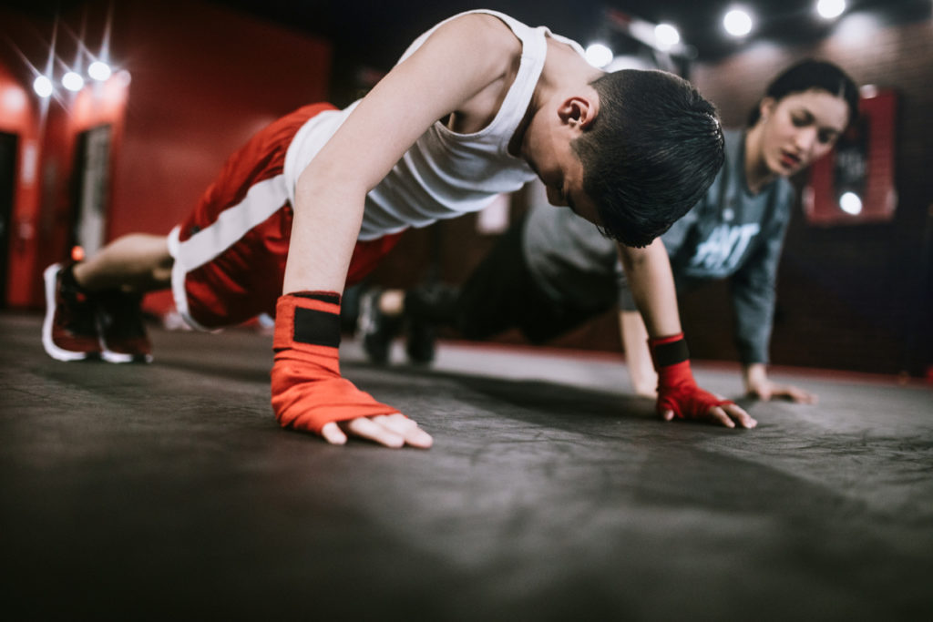 Young boy with red boxing hand wraps pushes himself through a press-up.