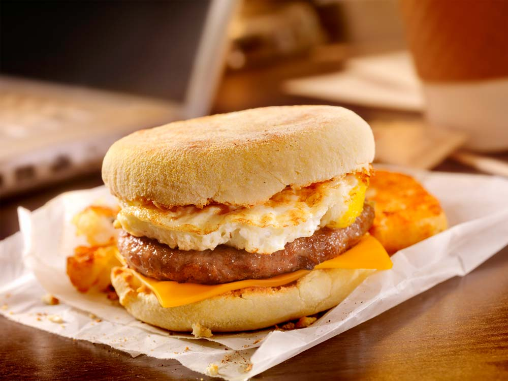 A close up of a fast food breakfast muffin with a hash brown.