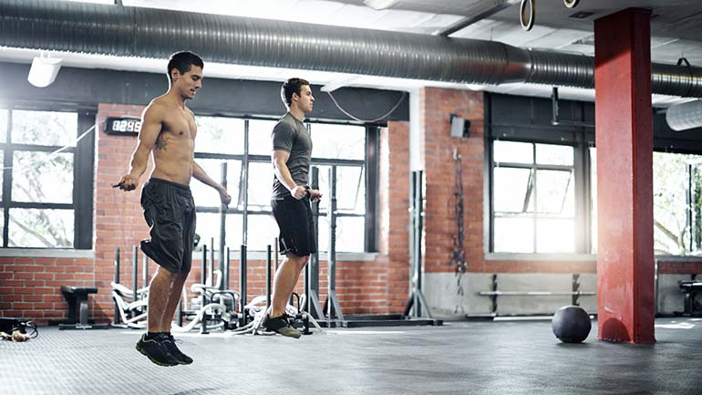 Shot of men jumping rope at the gym