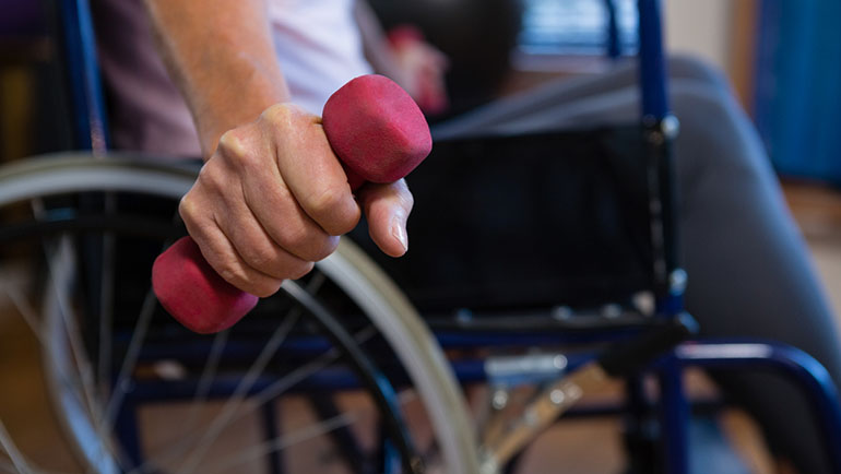Woman in wheelchair performing exercise with dumbbell in clinic