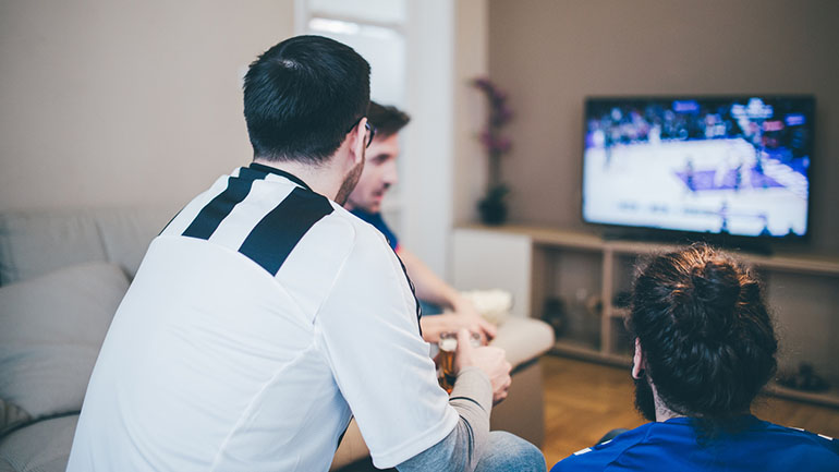 Three men talking and watching sports channel on TV