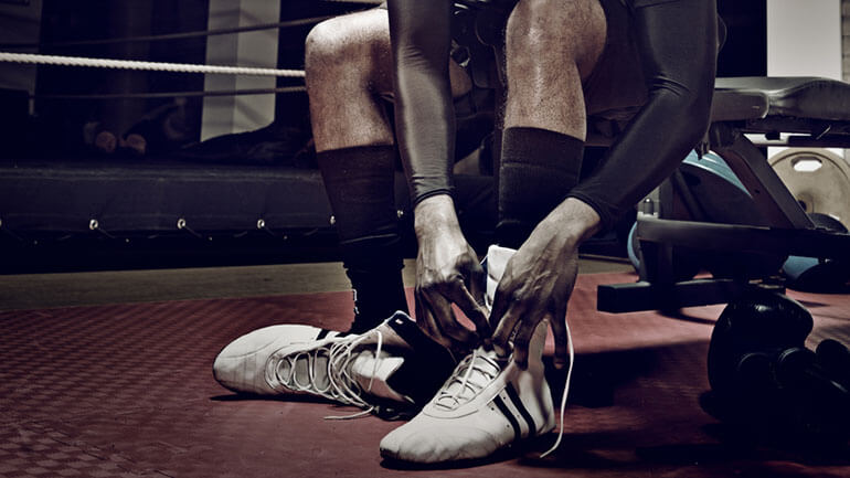man ties laces on boxing boots